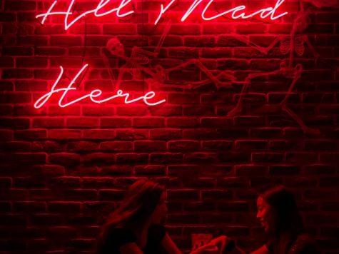 Women sitting under a neon sign